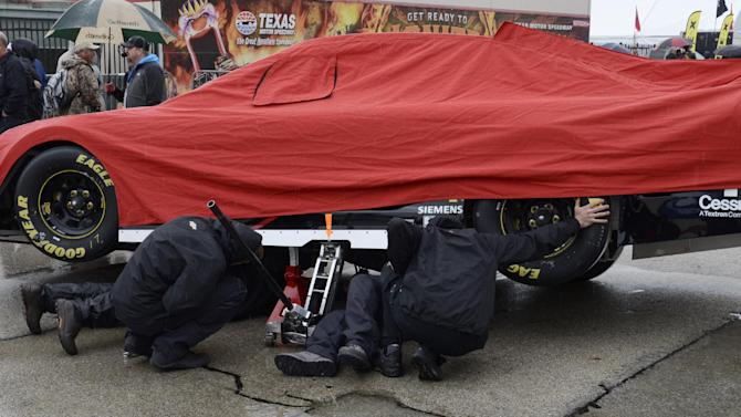 The crew for Jamie McMurray make final adjustments under their covered race car before the NASCAR Sprint Cup Series auto race at Texas Motor Speedway in Fort Worth, Texas, Sunday, April 6, 2014