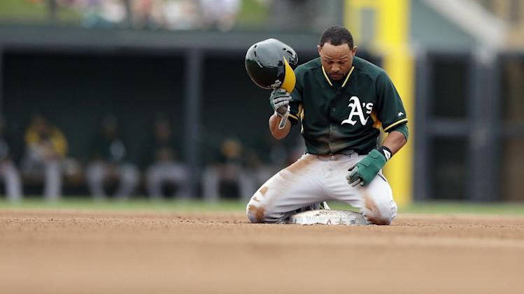 Oakland Athletics' Coco Crisp pauses after arriving safely to second, advancing off a ground out by teammate Jed Lowrie, during the fourth inning of an exhibition spring training baseball game against the Arizona Diamondbacks Thursday, March 6, 2014, in Scottsdale, Ariz. (AP Photo/Gregory Bull)