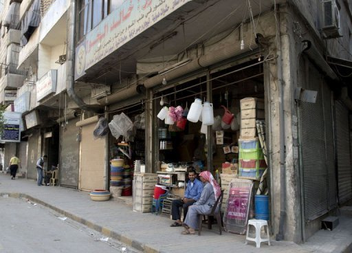 Syrian men sit in front of one of the few open shops in the Old City of Aleppo, northern Syria, on September 20. Despite the continuing fighting between rebel fighters and Syrian government forces, some shop owners defy the danger and open their shops, at least few hours a day