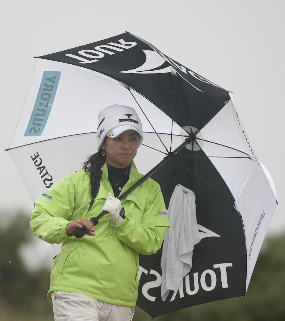 Japan's Ai Miyazato shelters from the rain during her final round at the Women's British Open golf championships at Royal Liverpool Golf Club, Hoylake, England, Sunday Sept. 16, 2012.  (AP Photo/Jon Super)