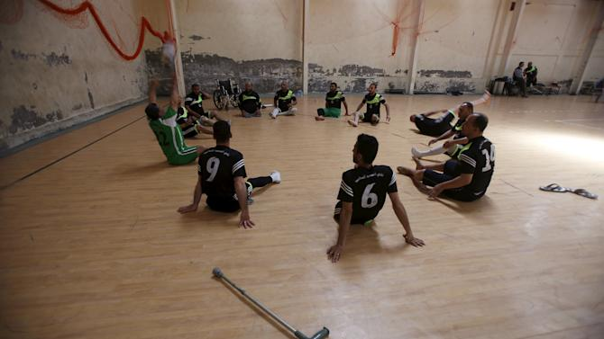 Disabled Palestinians warm up before taking part in a local sitting volleyball championship in Gaza City