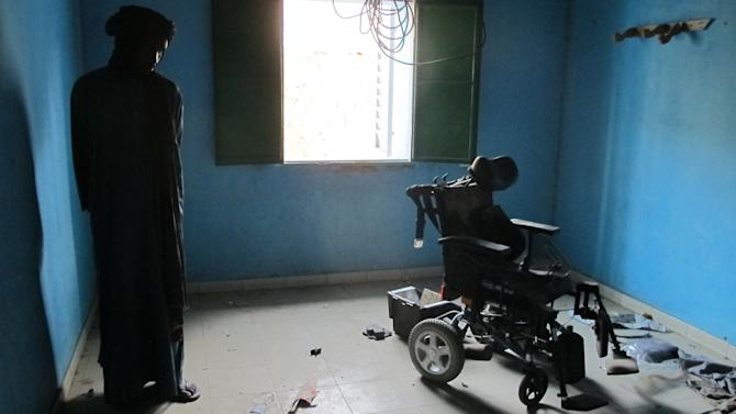 In this Wednesday, Feb. 6, 2013 photo, neighborhood resident Mohamed Alassane stands in a room where he and other residents say al Qaida held European hostages, at the Ministry of Finance's Regional Audit Department, in Timbuktu, Mali. Alassane and a doctor from the local hospital said the wheelchair had been used by an injured Islamist. In the same building, occupied by Islamists for more than a year, the AP found a more than 10-page letter signed by Abdelmalek Droukdel, the senior commander appointed by Osama bin Laden to run al-Qaida's branch in Africa. The confidential letter from the terror leader spelled out the terror network's blueprint for conquering this desert nation.(AP Photo/Rukmini Callimachi)