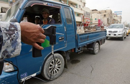 An Iraqi policeman uses a hand-held bomb and weapons detector in Baghdad in 2011. British prosecutors have charged six men with fraud for selling bomb detectors widely panned as ineffective that were sold to countries including Iraq, officials said Thursday