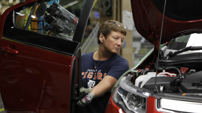 In this July 27, 2011 photo, assembly line worker Jan Primm manuevers a door into position for a 2012 Chevrolet Volt at the General Motors Hamtramck Assembly plant in Hamtramck, Mich. A private trade group says manufacturing activity barely grew in July, falling to the weakest level since just after the recession ended.(AP Photo/Paul Sancya)