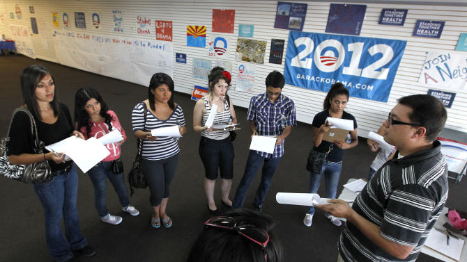 In this Friday, June 29, 2012 photo, Brian Conklin, far right, a regional campaign director for the reelection of President Barack Obama, briefs volunteers about registering new voters prior to them canvassing a heavily Latino neighborhood in Phoenix. Across the country both political parties have been courting the Latino vote, the nation's fastest-growing minority group.(AP Photo/Ross D. Franklin)