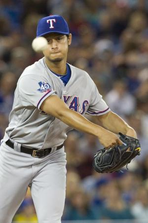 Texas Rangers pitcher Yu Darvish throws to first base to try and get out Toronto Blue Jays' Rajai Davis during fifth-inning baseball game action in Toronto, Friday, Aug. 17 , 2012. (AP Photo/The Canadian Press, Chris Young)