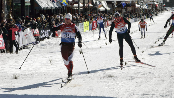 Santiago Ocariz, left, of Ely, Minn., crosses the finish line of the American Birkebeiner in Hayward, Wis., on Saturday, Feb. 22, 2014. Ocariz won the 54-kilometer Birkie Classic with a time of 3 hours, 1 minute, 0.8 seconds. (AP Photo/Paul M. Walsh)