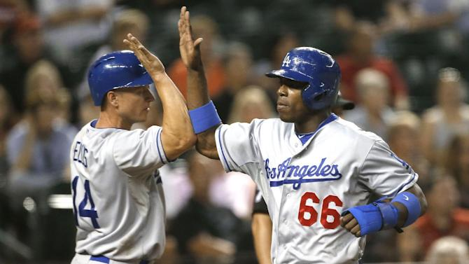 Los Angeles Dodgers' Yasiel Puig (66) and Mark Ellis high-five after scoring on a double by Hanley Ramirez during the fifth inning of a baseball game against the Arizona Diamondbacks, Wednesday, July 10, 2013, in Phoenix. (AP Photo/Matt York)