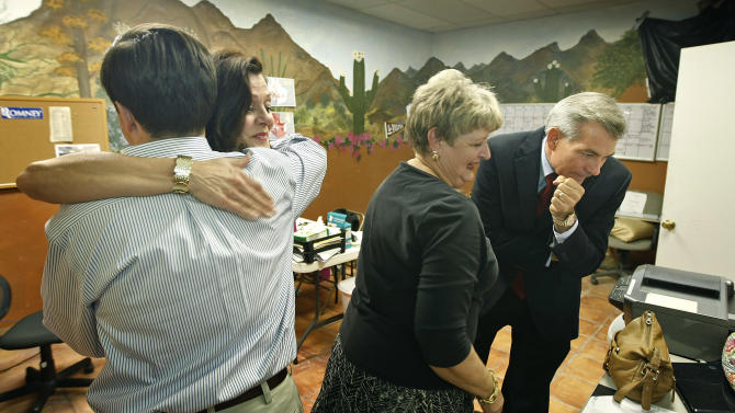 Congressional District 6 candidate Rep. David Schweikert, R-Arizona, right, looks over early election results with campaign events manager Allison Mary, center, as wife Joyce is congratulated by Schweikert's Chief of Staff Matt Tully, left, on the favorable results from his campaign headquarters on Tuesday, Aug. 28, 2012 in Phoenix. Schweikert and fellow Republican incumbent Rep. Ben Quayle have been locked in a spirited primary fight for the GOP nomination in the redrawn 6th District. (AP Photo/Ralph Freso)