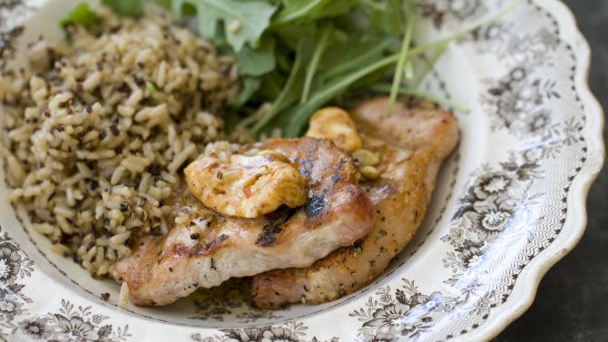This Sept. 30, 2013 photo shows pork chops with chipotle pumpkin seed butter in Concord, N.H. (AP Photo/Matthew Mead)