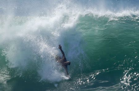 """A swimmer catches a wave at """"The Wedge"""" wave break in Newport Beach"""