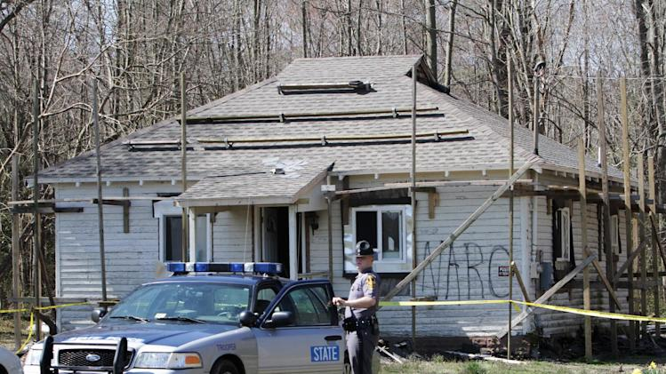 A state trooper stands guard in front of a house on Airport Drive in Melfa, Va. on Tuesday, April 2, 2013. One of two people being questioned about a fire at the house  has been charged in the blaze.  Tonya Susan Bundick, of Parksley, Va.,was charged this morning with one count of felony arson and one count of felony conspiracy to commit arson, said state police spokeswoman Corinne Geller.  ( Steve Earley / The Virginian-Pilot )  (AP Photo/The Virginian-Pilot, Stevve Earley)  MAGS OUT