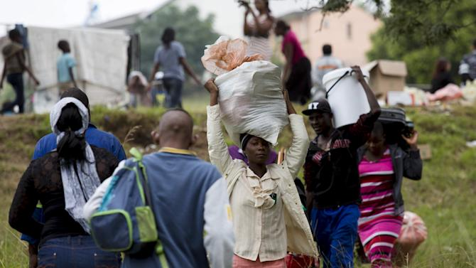 Foreigners from Zimbabwe carry their bags before boarding a bus home, from a camp for those affected by anti-immigrant violence in Chatsworth, north of Durban