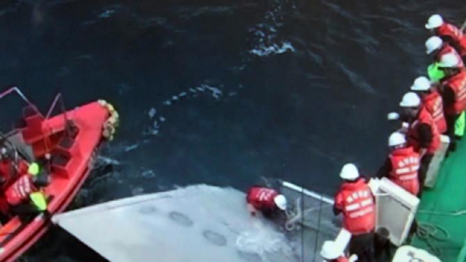 In this image made from video released by the Korea Coast Guard via Yonhap, South Korean coast guardsmen look at part of the wreckage of an Asiana Airlines cargo plane that crashed into the sea off Jeju Island, South Korea, on Thursday, July 28, 2011. The Boeing-747 cargo plane crashed into waters off the southern resort island of Jeju on Thursday, an airline official said. (AP Photo/ Korea Coast Guard via Yonhap) KOREA OUT