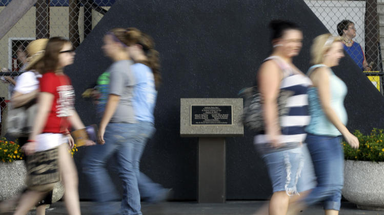 A memorial to the seven killed in the Aug. 13, 2011 stage collapse during a Sugarland concert at the Indiana State Fair, goes virtually unnoticed by fair visitors on opening day of the 2012 run of the State Fair in Indianapolis, Aug. 3, 2012.  (AP Photo/Michael Conroy)