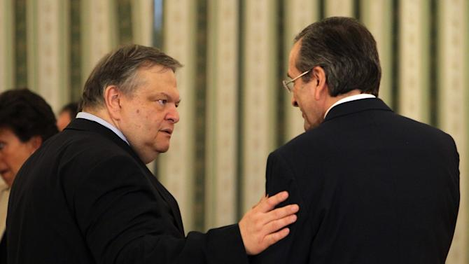 Greece's Prime Minister Antonis Samaras, right, and Socialist party head Evangelos Venizelos, who was named deputy prime minister and foreign minister speak to each other after a swearing in ceremony at the Presidential palace in Athens, Tuesday, June 25, 2013. Greece's new cabinet was sworn in Tuesday after a broad reshuffle in which conservative Prime Minister Antonis Samaras handed key posts to the coalition government's minority Socialist party following a political crisis. (AP Photo/Thanassis Stavrakis)