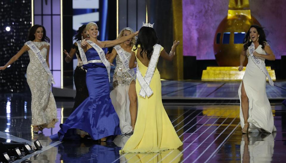Miss New York Nina Davuluri, center, is approached by contestants after Davuluri was crowned as Miss America 2014, Sunday, Sept. 15, 2013, in Atlantic City, N.J. (AP Photo/Mel Evans)