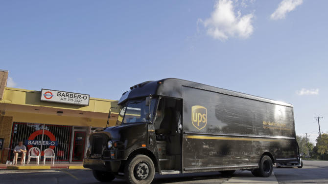 In this  Monday, Jan. 28, 2013, photo, a UPS truck arrives for a delivery Miami Springs, Fla. United Parcel Service Inc. says it was slowed down in the fourth quarter  of 2012, by weak global trade and a disappointing holiday-shopping season.  (AP Photo/Alan Diaz)