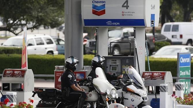 In this Thursday, Apr. 25, 2013, photo, Los Angeles Police police officers fill up at a Chevron gas station downtown Los Angeles. Chevron Corp. reports quarterly financial results before the market opens on Friday, April 26, 2013. (AP Photo/Damian Dovarganes)