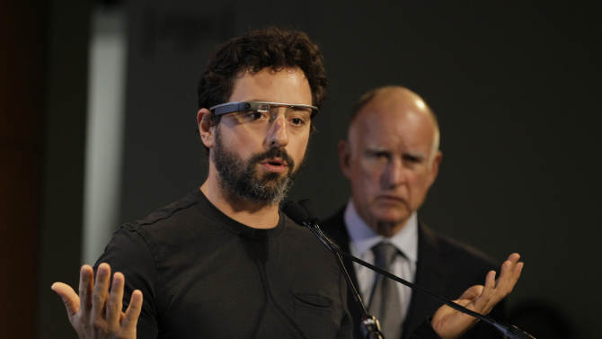 Google co-founder Sergey Brin, left, wearing internet glasses, gestures while speaking as California Gov. Edmund G. Brown Jr., right, listens during a bill signing for driverless cars at Google headquarters in Mountain View, Calif., Tuesday, Sept. 25, 2012.  The legislation will open the way for driverless cars in the state. Google, which has been developing autonomous car technology and lobbying for the legislation has a fleet of driverless cars that has logged more than 300,000 miles (482,780 kilometers) of self-driving on California roads. (AP Photo/Eric Risberg)