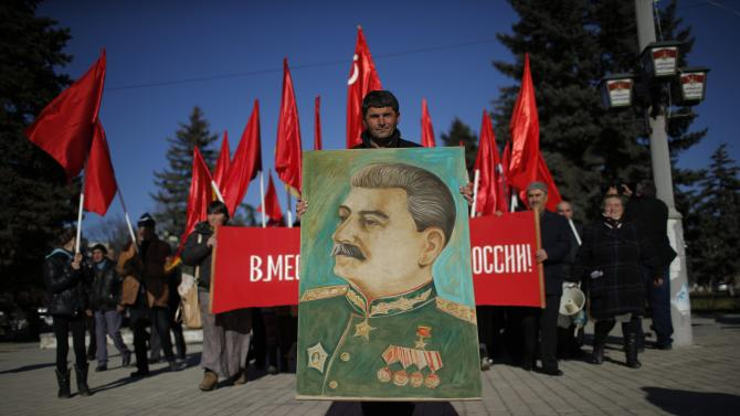 People march with red Soviet flags and portraits of Soviet dictator Josef Stalin during a rally marking Stalin's birthday anniversary at his hometown in Gori