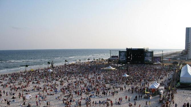 This May 20, 2011 photo shows festival goers on the beach at sunset at the Hangout Music Fest in Gulf Shores, Ala. Despite heat, humidity, crowds and costs, music festivals are more popular than ever, attracting millions of fans, with 270 festivals of various types annually in the U.S. and more than 800 in 57 countries. (AP Photo/Karen Schwartz)