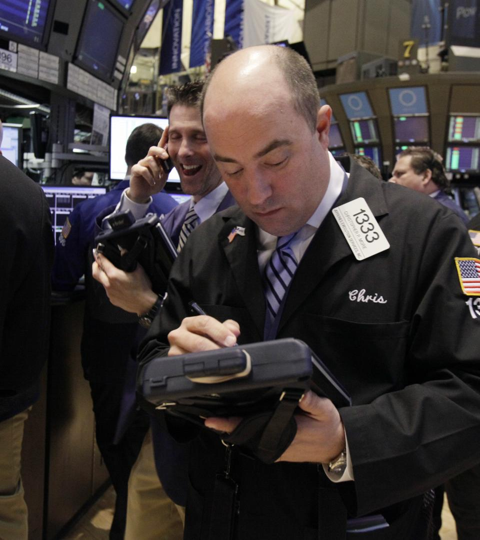 In a Tuesday March 13, 2012 photo Trader Christopher Morie, right, works on the floor of the New York Stock Exchange. Wall Street was poised for a higher opening Tuesday March 27, 2012, with Dow Jones industrial futures and S&P 500 both up. (AP Photo/Richard Drew)