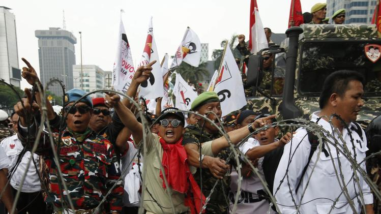 Supporters of presidential candidate Prabowo Subianto shout at police as they try to reach the Constitutional Court in Jakarta