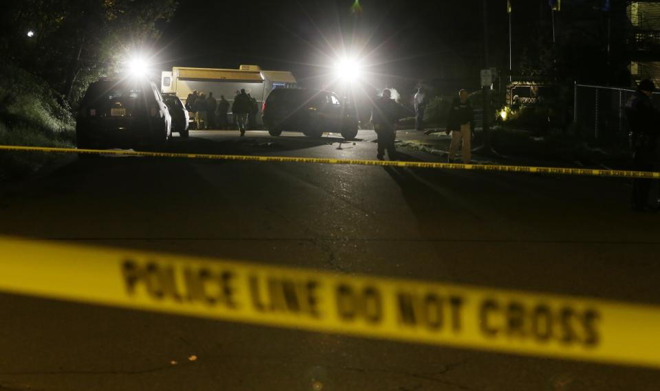 Crime-scene tape is shown as investigators work under lights at the scene of an overnight shooting that left five people dead, including a suspect who was shot by arriving officers, police said early Monday, April 22, 2013, at the Pinewood Village apartment complex in Federal Way, Wash. (AP Photo/Ted S. Warren)