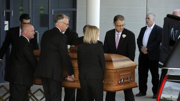 The casket containing William Corporon is carried into a hearst after the funeral for him and his grandson in Leawood