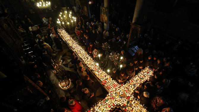Worshippers gather around candles stuck to jars with honey, during a religious mass in the church of the Presentation of the Blessed Virgin in Blagoevgrad