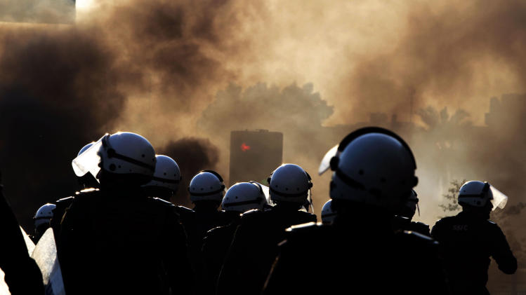 Riot police watch for Bahraini anti-government protesters, unseen, near tire fires set by protesters in Sanabis, Bahrain, on Friday, Oct. 5, 2012. Riot police used water cannons and tear gas on Friday to disperse hundreds of anti-government protesters trying to reach a heavily guarded site that was once the hub of their uprising. (AP Photo/Hasan Jamali)