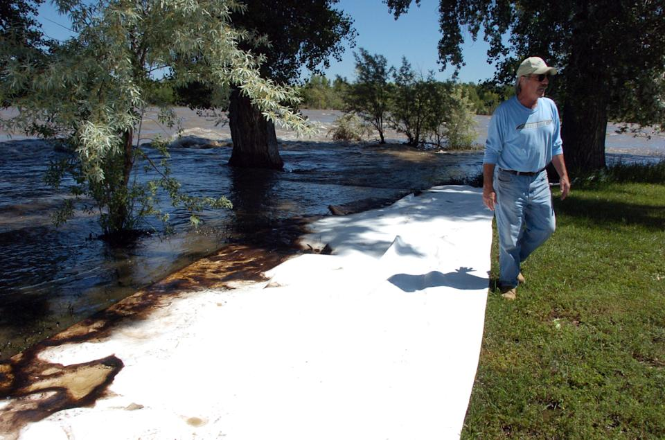 Jim Swanson is seen in his yard east of Laurel, Mont. where absorbent sheets were laid down to soak up oil from a ruptured ExxonMobil pipeline beneath the Yellowstone River Saturday July 2, 2011. (AP Photo/Matthew Brown)