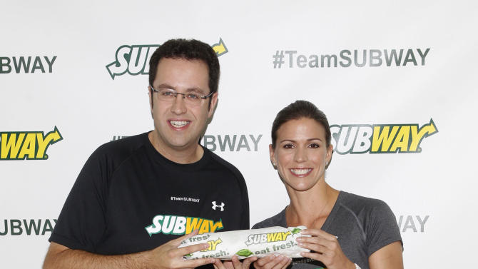 """Former Team SUBWAY marathoner Jared Fogle """"The SUBWAY Guy,"""" passes the Footlong baton to Whitney Phelps, sister of Olympic swimming champion Michael Phelps, as Whitney announces that she will run the ING New York City Marathon with Team SUBWAY at the Chelsea Piers Sport Center, Monday, Oct. 15, 2012 in New York. (Photo by Jason DeCrow/Invision for SUBWAY/AP Images)"""