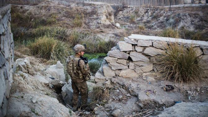A U.S. soldier from Grim Company of the 3rd Cavalry Regiment stands guard near an Afghan police checkpoint near Forward Operating Base Fenty in the Nangarhar province of Afghanistan