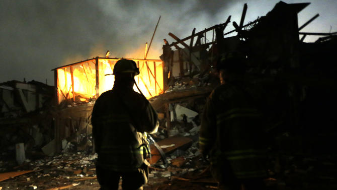 Firefighters use flashlights early Thursday morning, April 18, 2013 to search a destroyed apartment complex near a fertilizer plant that exploded Wednesday night in West, Texas. The massive explosion killed as many as 15 people and injured more than 160, shaking the ground with the strength of a small earthquake and leveling homes and businesses for blocks in every direction. (AP Photo/LM Otero)