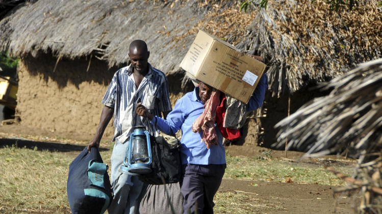 A man and his brother carry their belongings as they leave the area following clashes, near Chamwanamuma village in the Tana River delta of southeastern Kenya Thursday, Sept. 13, 2012. An international rights group says Kenyan authorities should expand investigations into the alleged roles of three politicians in clashes in Kenya's southeast which have killed at least 110 people in three weeks. (AP Photo)