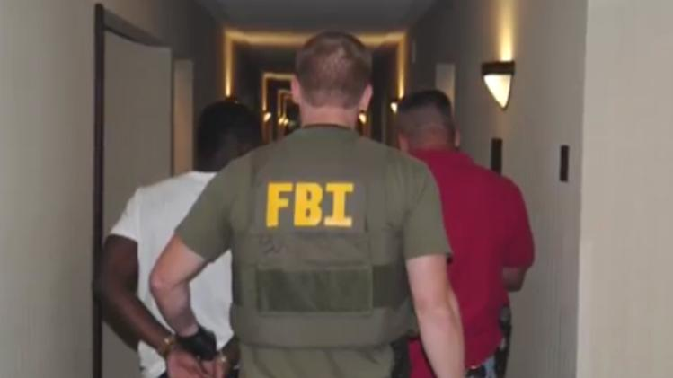 In this June, 2014 image from video provided by the FBI, authorities raid a hotel in Jackson, Mississippi. When FBI agents and police officers fanned out across the country last month in a weeklong effort to rescue child sex trafficking victims, they pulled kids as young as 11 from dingy motel rooms, truck stops and homes. (AP Photo/FBI)