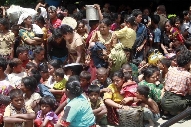 Muslims women and children from villages gather before being relocated to secure areas in Sittwe, capital of Rakhine state in western Myanmar, where sectarian violence is ongoing Tuesday, June 12, 201