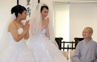 Taiwanese women Fish Huang (L) and her partner You Ya-ting accept the blessing from Master Shih Chao-hui during their same-sex Buddhist wedding ceremony in Taoyuan, on August 11. The two women tied the knot in Taiwan's first same-sex Buddhist wedding, a move rights groups hope will help make the island the first society in Asia to legalise gay marriage. (AFP Photo/Sam Yeh)
