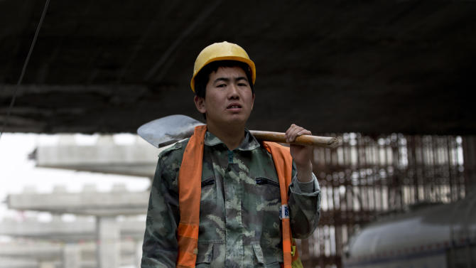 A worker prepares to construct a city highway which is under construction in Beijing Monday, April 15, 2013. China's economic growth slowed unexpectedly in the first three months of the year, fueling concern about the strength of its shaky recovery. The world's second-largest economy grew by 7.7 percent over a year earlier, down from the previous quarter's 7.9 percent, the government reported Monday.  (AP Photo/Andy Wong)