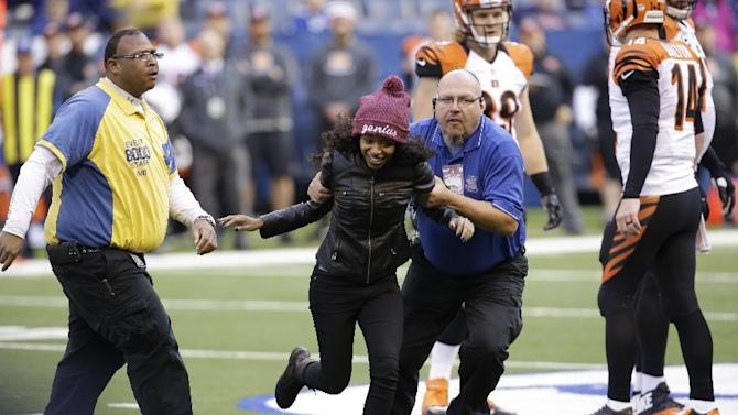 Security escorts a fan off the field during the second half of an NFL football game between the Indianapolis Colts and the Cincinnati Bengals Sunday, Oct. 19, 2014, in Indianapolis. (AP Photo/AJ Mast)