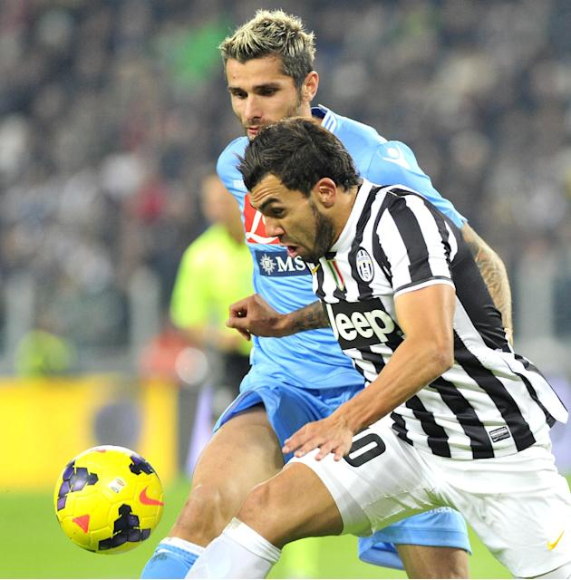 Juventus forward Carlos Tevez, of Argentina, challenges for  the ball with Napoli's Valon Berhami, during a Serie A soccer match between Juventus and Napoli at the Juventus stadium, in Turin, Italy, S