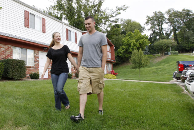 In this Monday, Aug. 20, 2012 photo, Marine Sgt. Ron Strang, right, walks with his girlfriend, Monica Michna, in the yard by his home in Jefferson Hills, Pa., just south of Pittsburgh. In 2008, the fe