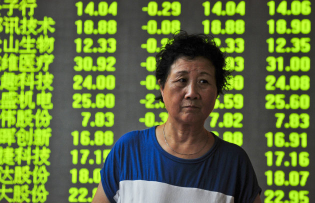 A woman walks past a screen showing the China Composite Stock Price Index at a brokerage house in Shenyang in northeast China's Liaoning province Monday, Aug. 13, 2012. World stock markets fell Monday after a slowdown in Japan's growth gave investors another reason to worry about the health of the global economy. (AP Photo) CHINA OUT