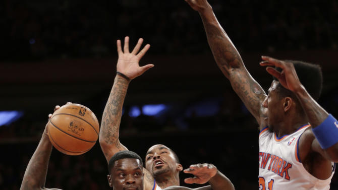 Indiana Pacers' Lance Stephenson, left, drives to the basket underneath New York Knicks' Iman Shumpert, right, and J.R. Smith during the first half of the NBA basketball game, Sunday, April 14, 2013, in New York. (AP Photo/Seth Wenig)