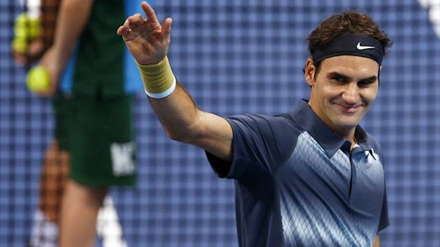 Switzerland's Roger Federer waves after winning his quarter final match against Grigor Dimitrov of Bulgaria at the Swiss Indoors ATP tennis tournament in Basel October 25, 2013. REUTERS