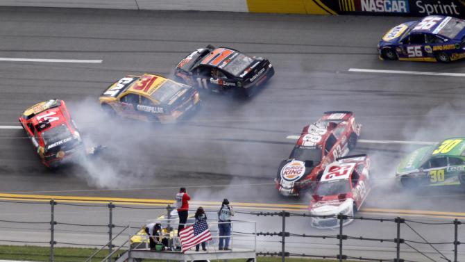 Cars spin through Turn 1 in a multi-car wreck during the NASCAR Sprint Cup Series Aaron's 499 auto race at Talladega Superspeedway in Talladega, Ala., Sunday, May 5, 2013. Tony Stewart (14), Jeff Burton (31), Brian Vickers (11), David Reutimann (83), Kevin Harvick (29), David Stremme (30) and Martin Truex Jr., all participate in the wreck. (AP Photo/Butch Dill)