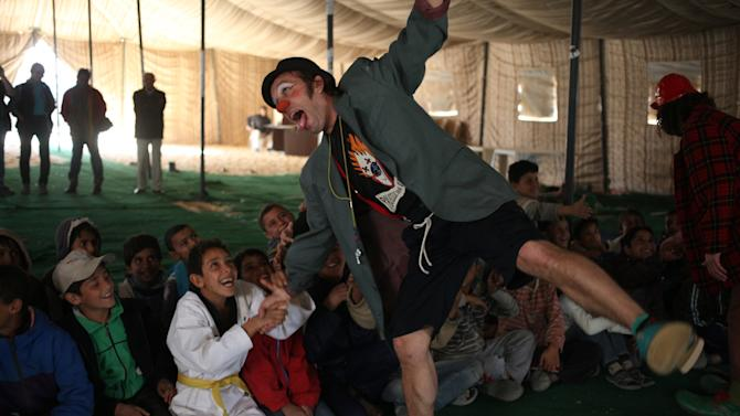 Moises Queralt, a clown from Mabsutins, a group of clowns from Spain, acts weak as a Syrian refugee child in a karate uniform pulls his arm during their show at Zaatari refugee camp near the Syrian border in Mafraq, Jordan, Sunday, Dec. 1, 2013. It was an unusual day for Syrian refugee children: Pinocchio and other show gigs live Sunday under a wind-swept tent in a sprawling desert camp straddling the Syrian border. (AP Photo/Mohammad Hannon)