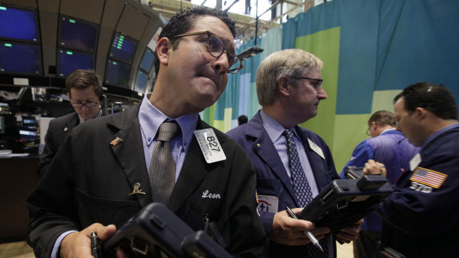 Leon Montana, left, works with fellow traders on the floor of the New York Stock Exchange Wednesday, June 20, 2012. Stocks edged lower early Wednesday after investors saw signs that economies could be slowing down in both the West and China. (AP Photo/Richard Drew)